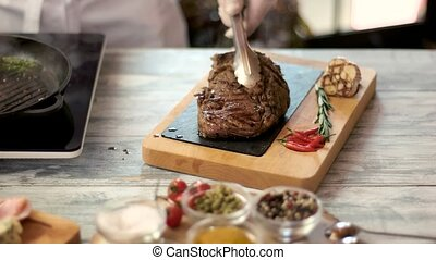Grilled ribeye steak on board. Hand of chef with tongs.