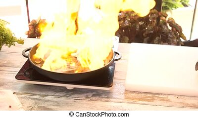 Preparing flambe steak. Frying pan and wooden table.