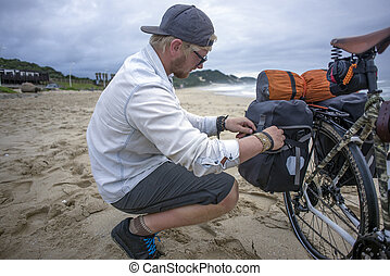 Long Distance Cyclist Prepares Panniers while on Beach - A...