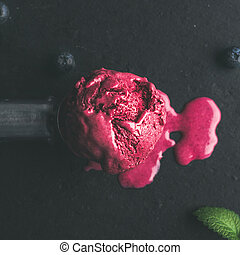 Melting scoop of blueberry ice-cream over black background,...