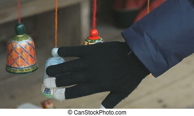 Human hand touching colorful russian wooden bells - Human...