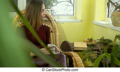 lovely young girl sitting in a wicker chair at home looking...