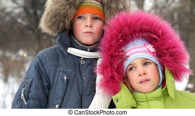 boy and girl against wood in winter