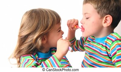 boy and girl brush teeth looking against each other, then...