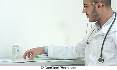 Young doctor in glasses showing medical results to his...