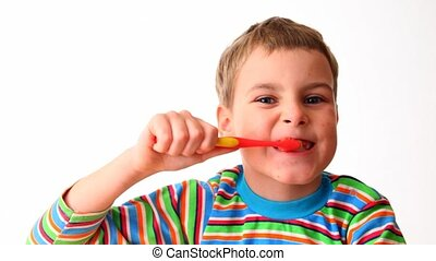 boy cleans teeth red tooth-brush - little boy in striped...