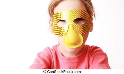 girl in gold mask with nose looks in camera, smiles and...