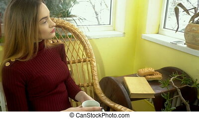 young woman sitting at home in a wicker chair looking out...