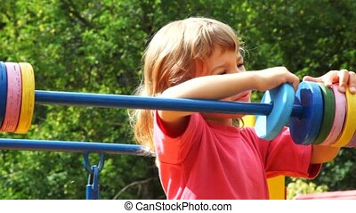 girl on playground moves wheels on pipe