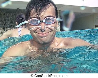 man in goggles diving into outdoor water pool - smiling...