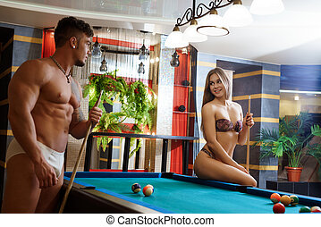 Young couple in love playing  billiards at spa