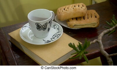 close up of girl takes a hot cup of coffee with a wooden table