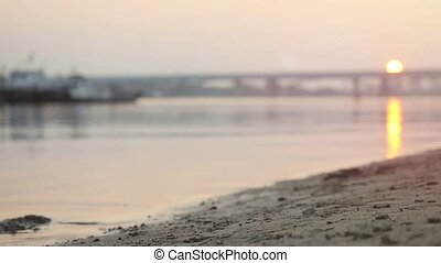Close up of athletic man running on the beach at sunset in...