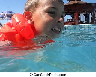 boy in inflatable jacket swims in water pool - smiling boy...