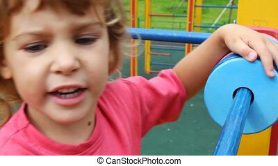 girl moves on playground - little girl moves on one hand on...