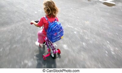 girl k goes on four-wheel bicycle - little girl in pink and...