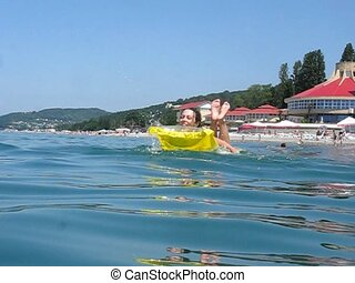 woman on inflatable mattress oars in sea