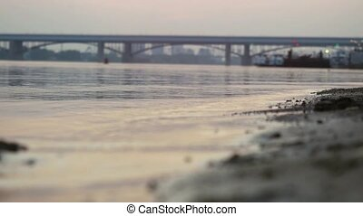 Sea, sand, ocean sunset with bridge, city on background. -...