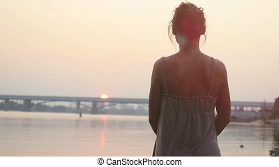 Young woman standing on sandy beach, watching sun going down...