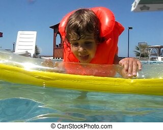 girl on inflatable mattress in water pool - little girl with...