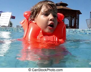 girl in life jacket swims in outdoor water pool