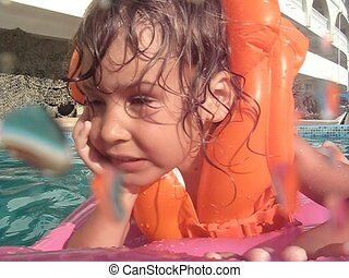girl lies on inflatable mattress in water pool - little girl...
