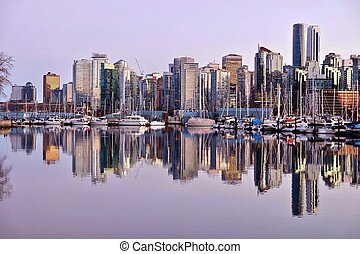 Vancouver skyline and reflection in water.