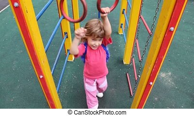 girl on playground approaches to rings and hangs on them -...