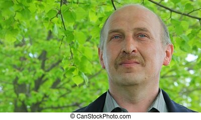 smiling man with moustache stands under tree - portrait of...