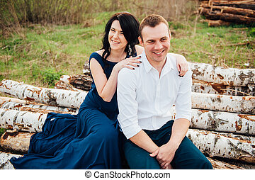 happy couple in love sitting on a log and laughing.
