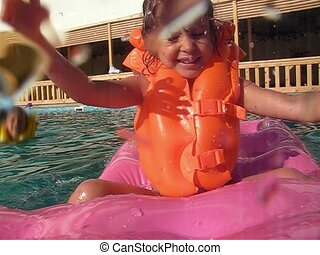 girl sits on inflatable mattress in water pool