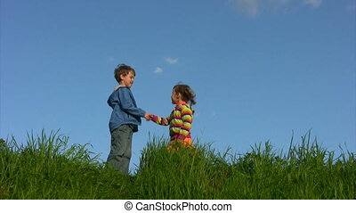 boy and girl meeting and handshaking in meadow