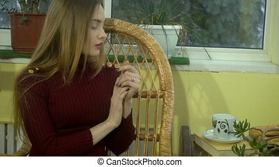 Cutie young girl with beautiful make up sits in wicker chair...
