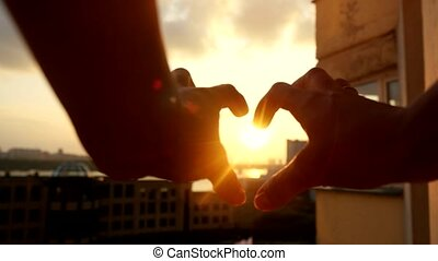 Woman's hands making a heart through the sun at amazing...