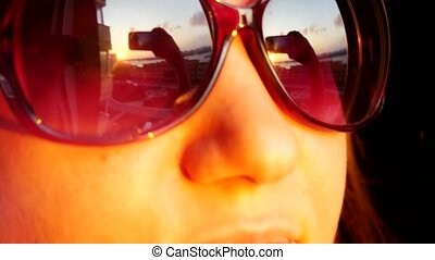 Close up of view young woman's face in sunglasses, standing at window and holding smartphone takes picture on sunset in the city background. That reflected in her sunglasses. 3840x2160
