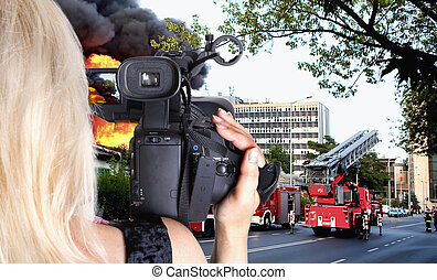 Woman videgrapher recording big fire in the city