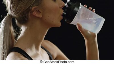Fit and sporty blonde woman in workout outfit drinking water...