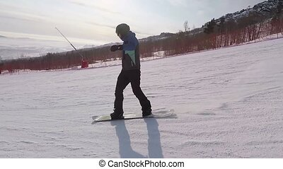 The snowboarder in ski resort. The athlete cuts on the...