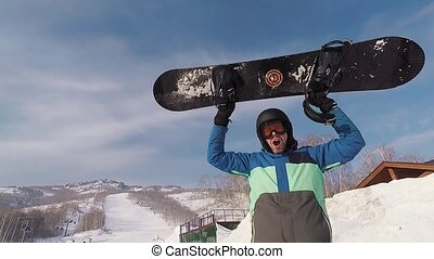 Adult bearded man standing in the ski park. He held up a...