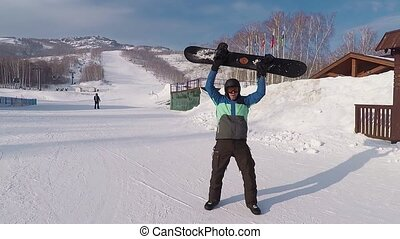 Happy male snowboarder with snowboard in his hands is standing on ski resort and dancing happily. Man in winter outfit is having fun and rising hands with the board on the mountain slope.