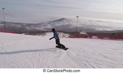 Back view of young snowboarder quickly sliding down on the...