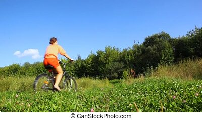 woman rides bicycle from camera in field