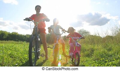 family sits on bicycles in park - happy family of three sits...