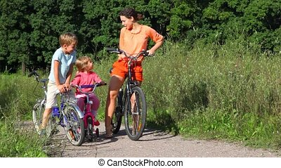 mother and kids sits on bicycles in park