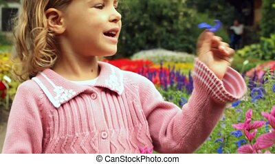 girl stands on path in botanical park among colours and...
