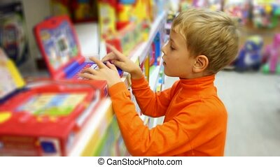 boy pushes buttons of electonic toy in shop - smiling boy...