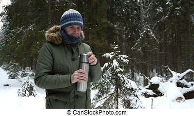 Man putting hot drink into a cup in a winter forest - Man in...
