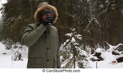 Man drinking tea in a winter forest