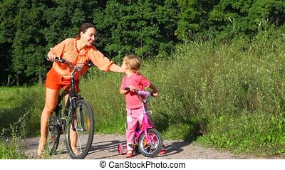 mother pats on the back daughter, then both of them rides bicycles