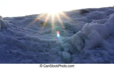 the warm sun shines through the cold snow-covered mountains in the camera lens